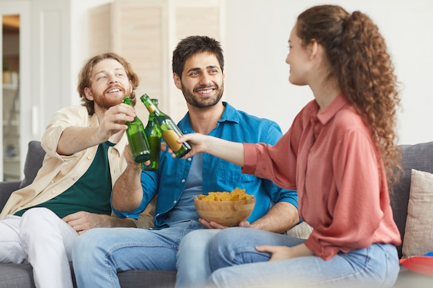 Group of friends clinking beer bottles while watching tv together sitting on comfortable sofa at home