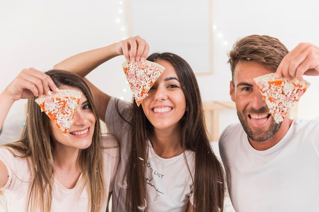 Group of friends covering their one eyes with slice of pizza