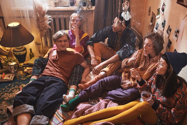 Group of friends doing bad things during domestic party they smoking and drinking