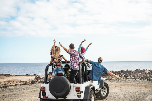 Group of friends doing excursion around desert with convertible 4x4 car - friendship, tour, youth, lifestyle and vacation concept - focus on guys bodies