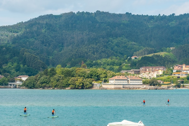 A group of friends doing paddle surfing in the sea in urdaibai, a bizkaia biosphere reserve next to mundaka. basque country