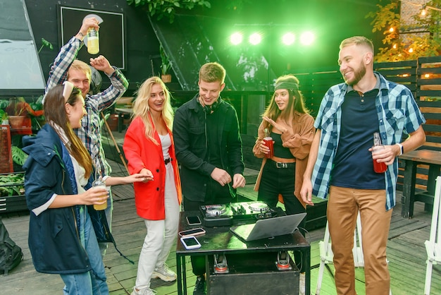 Group of friends drinking beer, dancing to the music, chatting and having a good rest time at outdoor summer party.