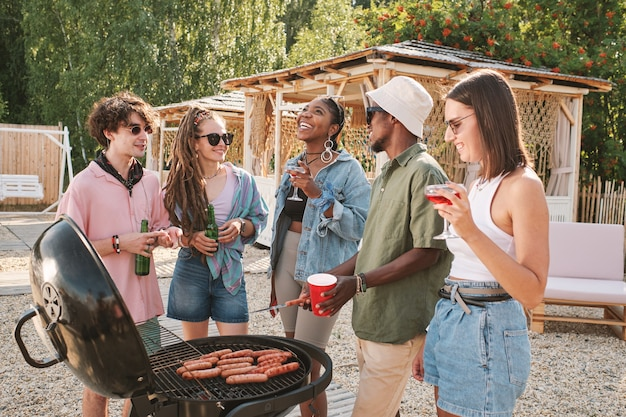 Group of friends drinking beer grilling hot dogs and joking around at beach party on summer day