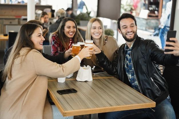 Группа друзей пьет пиво, делая селфи с мобильным телефоном в баре-пивоварне - сосредоточьтесь на лице человека