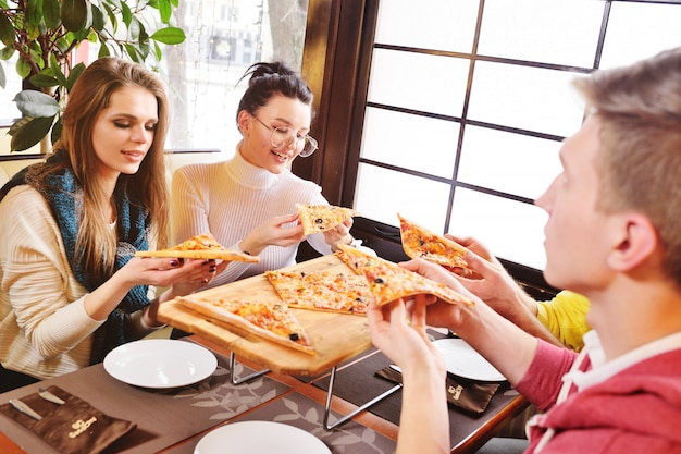 A group of friends eat fresh delicious pizza in a cafe, talk and laugh.