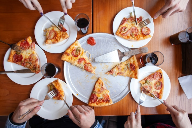 Group of friends eating italian pizza