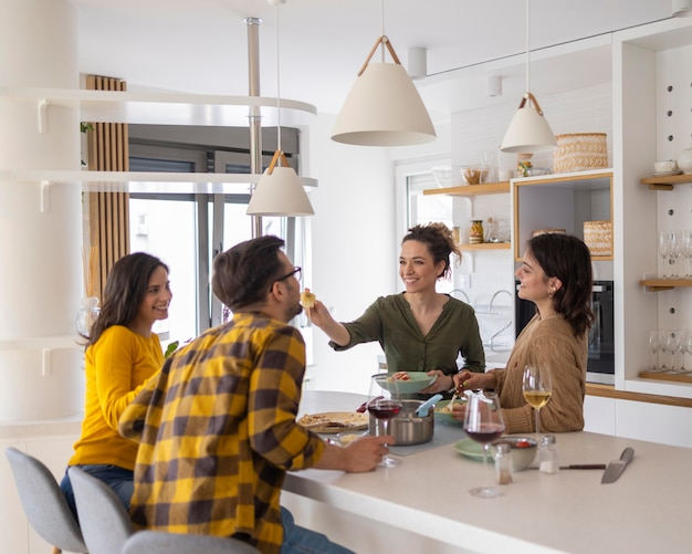 Group of friends eating pasta together in the kitchen