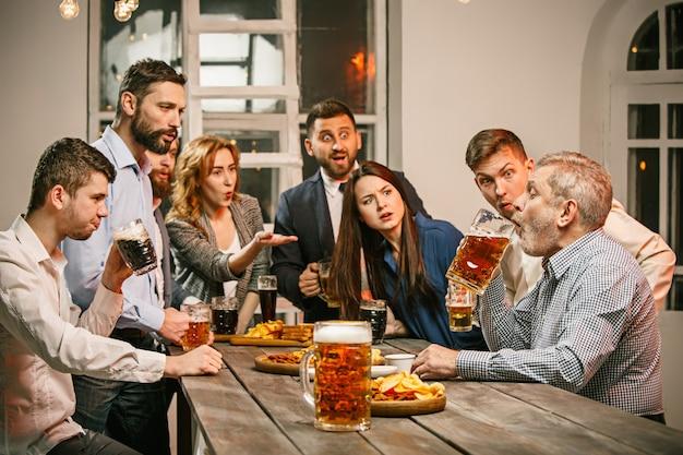 Gruppo di amici che godono di un drink serale con la birra