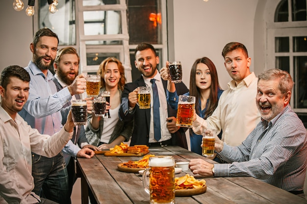 Group of friends enjoying evening drinks with beer