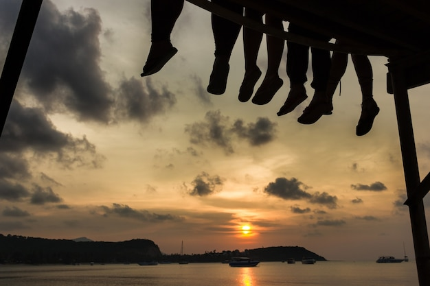 Group of friends enjoying a warm sunset while sitting on the dock of the bay in the island of koh samui, thailand. silhouettes of people legs at candid twilight by the sea. chill out, relax concept