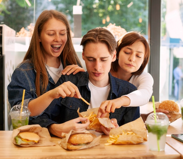 Group of friends at fast food restaurant eating burgers