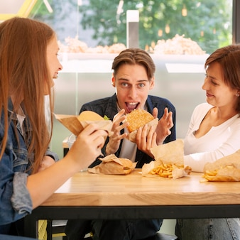 Gruppo di amici al ristorante fast food che mangia cheeseburger