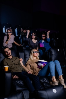 Group of friends and girlfriend trying to wake up tired guy napping in armchair in cinema during movie