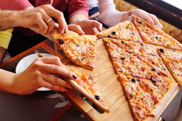 A group of friends grab a fresh hot pizza sitting in a cafe.