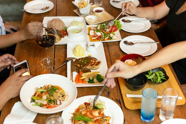 Group of friends hands with fork having fun eating variety food on the table.