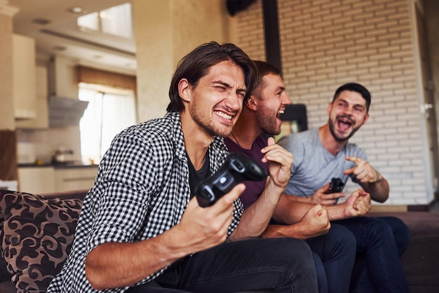 Group of friends have fun playing console game indoors at living room.