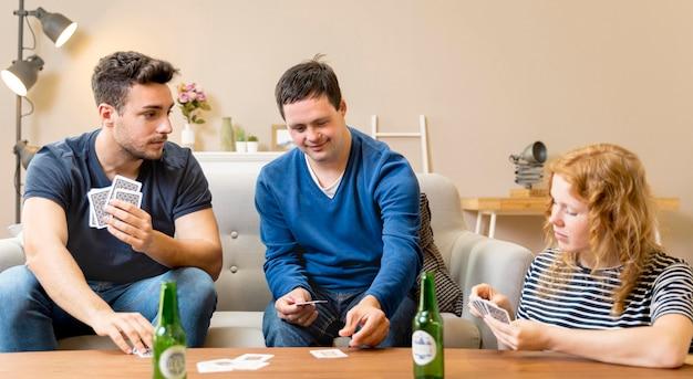 Gruppo di amici che mangiano birra e carte da gioco a casa