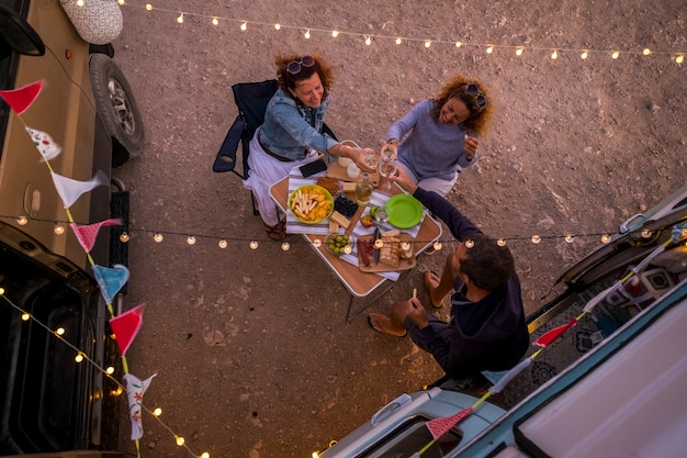 Group of friends having dinner together in friendship outside little van - alternative travel lifestyle and vehicle vacation - people having fun and enjoy the freedom and the adventure - vertical view