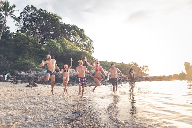 Group of friends having fun on the beach on a lonely island