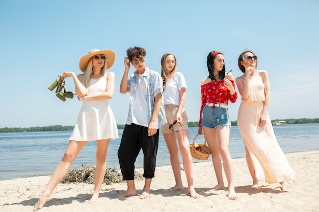 Group of friends having fun on the beach in sunny summer day