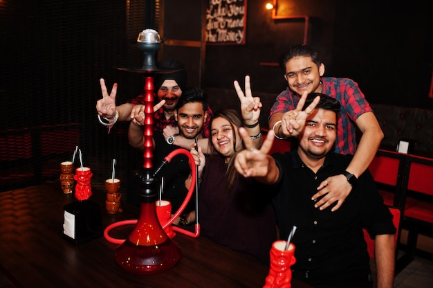 Group of friends having fun and rest at night club, drinking cocktails and smoke hookah hands with two fingers up.