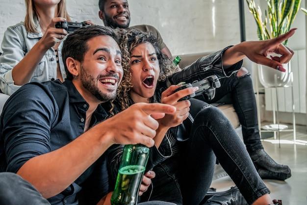 Gruppo di amici che si divertono mentre giocano ai videogiochi insieme a casa. concetto di amici.