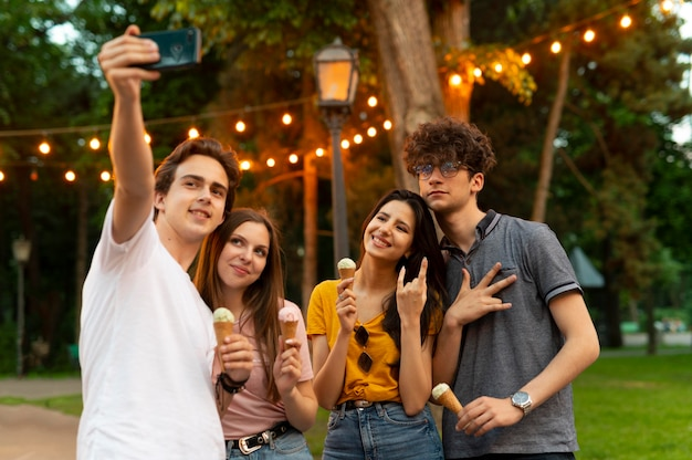 Gruppo di amici che mangiano un gelato all'aperto e si fanno selfie