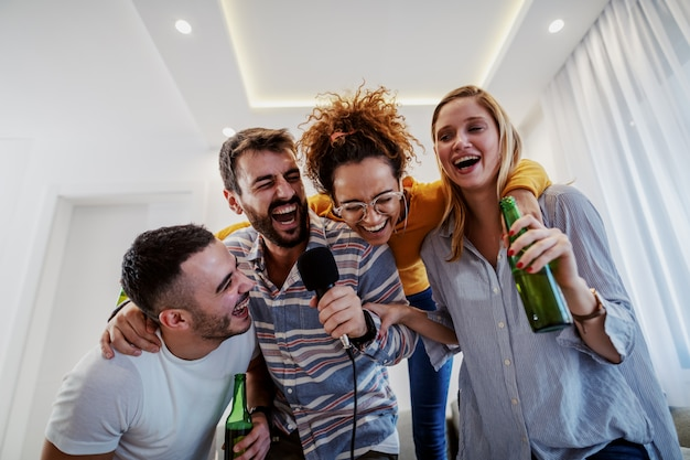 Group of friends having karaoke party at home. man holding microphone while other ones holding beer.