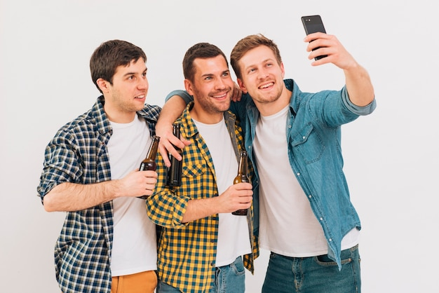 Group of friends holding beer bottle taking selfie on mobile phone against white backdrop