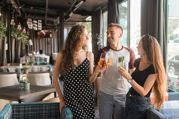 Group of friends holding different type of alcohol drinks in restaurant