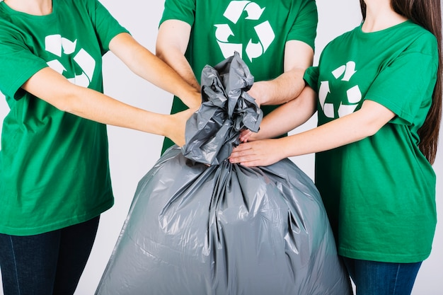 Group of friends holding garbage bag