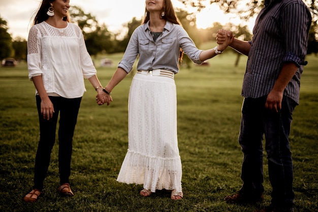 Group of friends holding hands in the park and praying