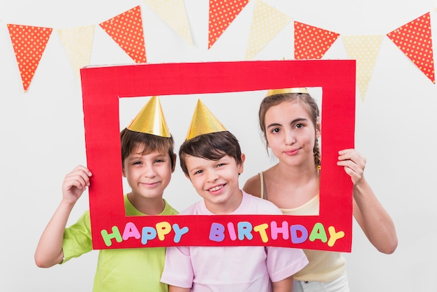 Group of friends holding happy birthday frame wearing party hat