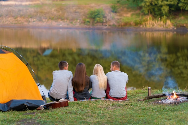 A group of friends is enjoying view, camping with bonfire on riverside