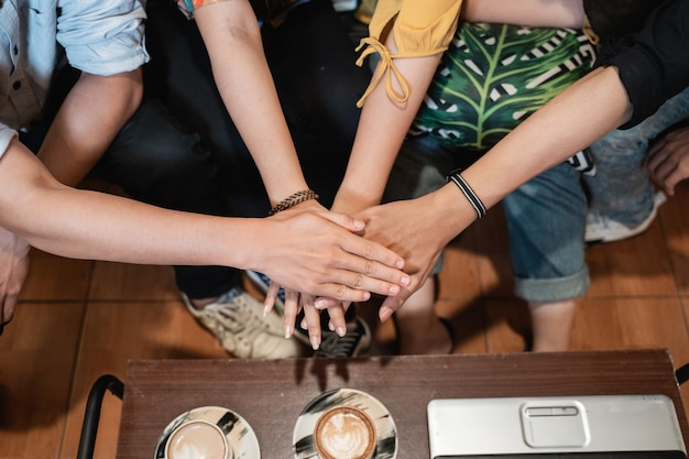 Group of friends joining hands with unity teamwork concept when hang out in coffee shop