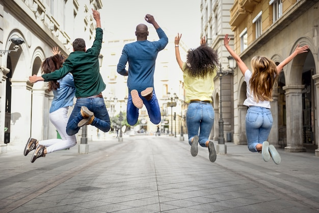 Group of friends jumping together outdoors