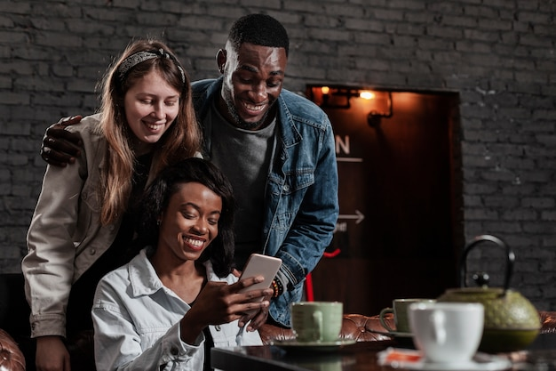 Group of friends laughing at phone