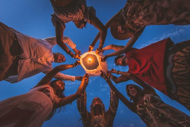Group of friends lighting lanterns