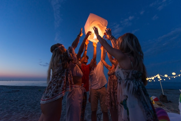 Group of friends lighting lanterns