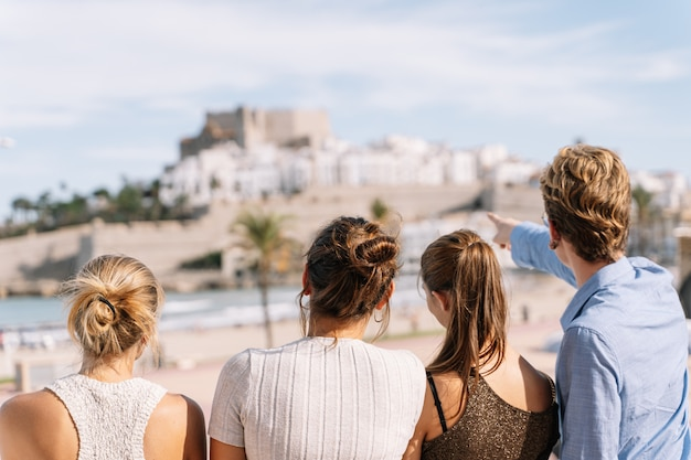 Group of friends looking at the city of peniscola during a trip through spain