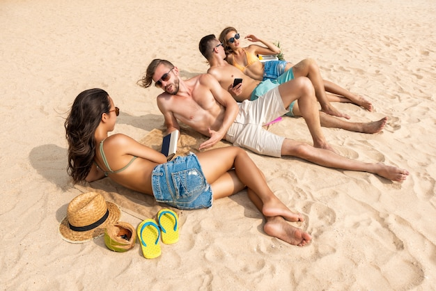 Group of friends lying at the beach taking a sunbath