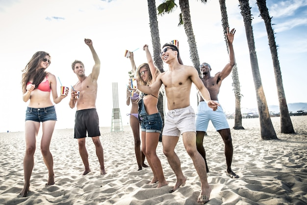 Group of friends making big party on the beach