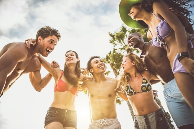 Group of friends making big party and games on the beach
