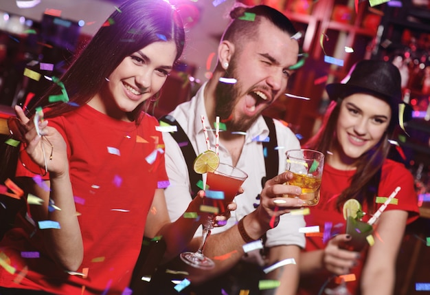 A group of friends at a party in a nightclub clink glasses with alcoholic beverages.