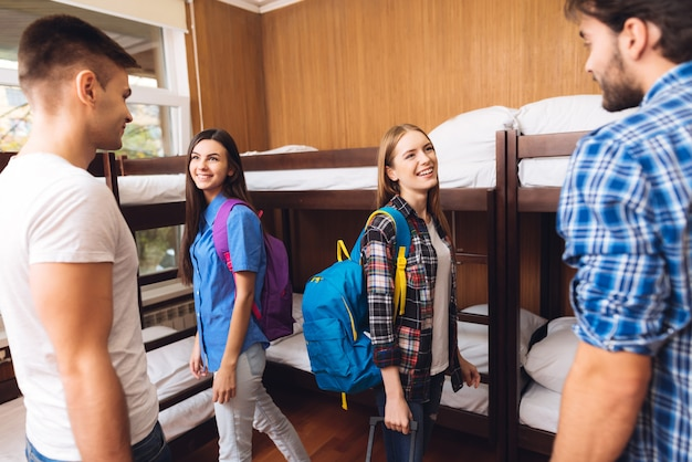 Group of friends in plaid shirts in hostel.