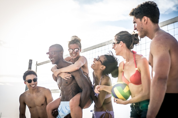 Group of friends playing beach volley on the beach.