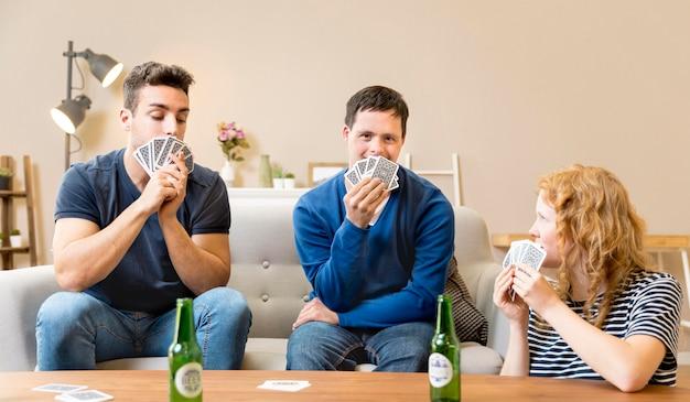Gruppo di amici che giocano a carte a casa e che mangiano birra