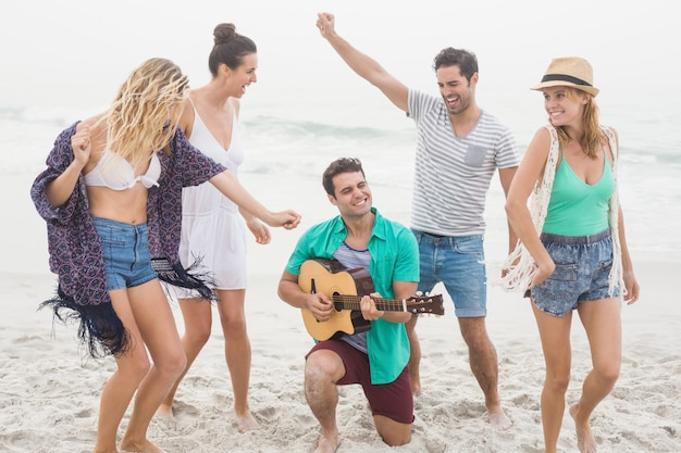 Group of friends playing guitar and dancing