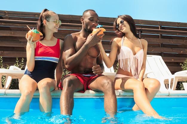 Gruppo di amici che giocano e che si rilassano in una piscina durante le vacanze estive