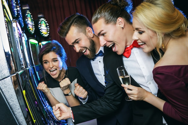 Group of friends playing slot machines